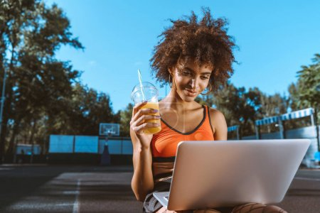 african-american woman with laptop and juice