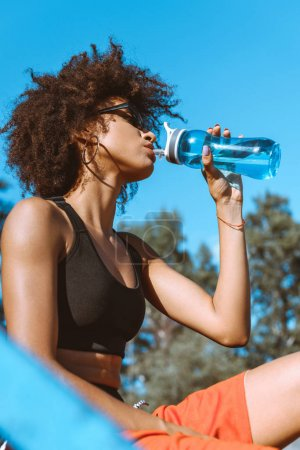 Photo for Young african-american woman in sportive attire drinking from blue water bottle - Royalty Free Image