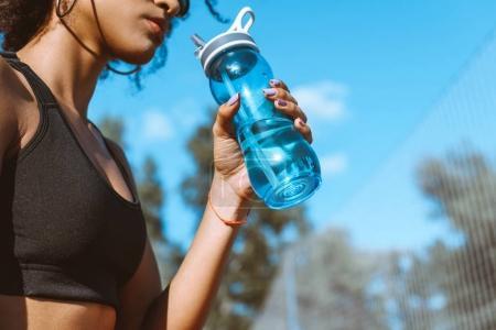 Photo pour Plan recadré de femme en soutien-gorge de sport buvant de bouteille d'eau bleue - image libre de droit