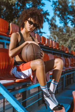 african-american woman in bleachers with basketball