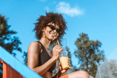 Photo for Young african-american woman in sports bra sitting in the bleachers and holding orange juice - Royalty Free Image