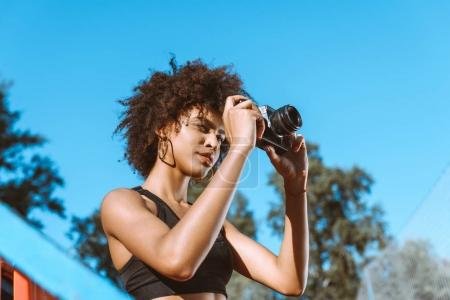 Athletic african-american woman with camera