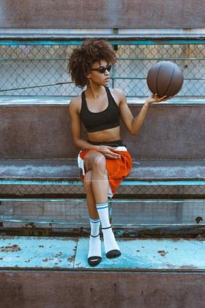 Woman in sportswear and heels with basketball