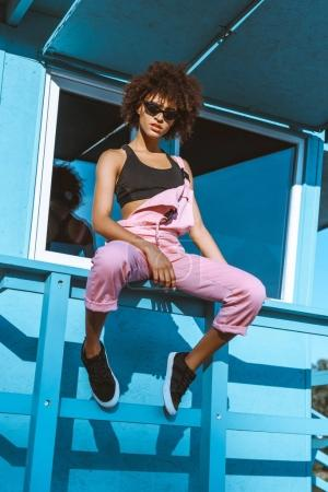 African-american woman in sports bra and overalls