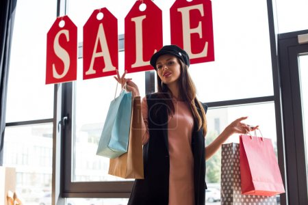 Photo for Low angle view of smiling young woman holding shopping bags and looking at camera in boutique - Royalty Free Image