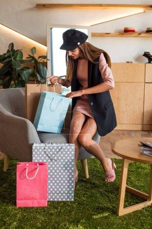 Photo pour Belle jeune femme, sacs à provisions en regardant tout en étant assis sur la chaise en boutique - image libre de droit