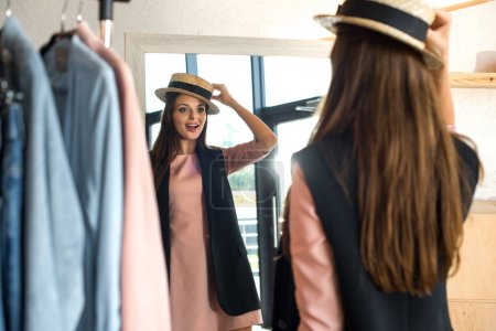 Girl trying on hat in boutique