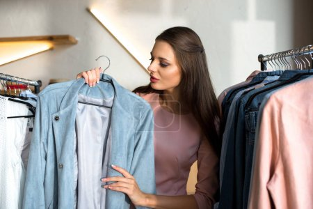 Photo for Attractive young woman choosing stylish clothes in store - Royalty Free Image