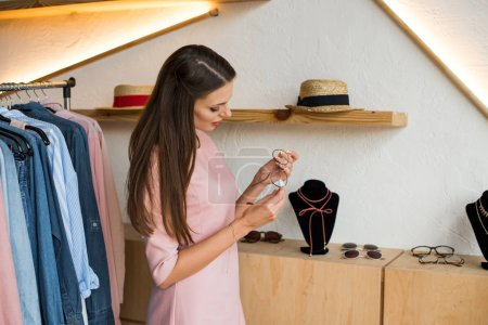 Photo for Beautiful young woman holding stylish eyeglasses in store - Royalty Free Image
