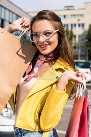 Photo for Happy attractive young woman in spectacles holding shopping bags and smiling at camera - Royalty Free Image