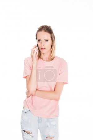Photo for Concerned woman in pink t-shirt talking on phone, isolated on white - Royalty Free Image