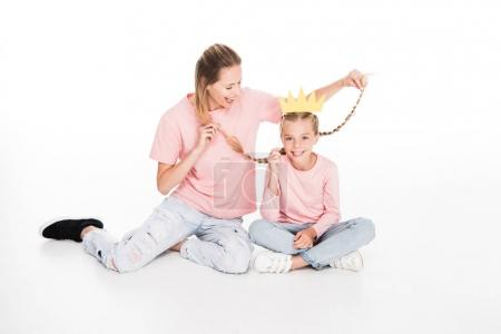 mother holding braids of daughter