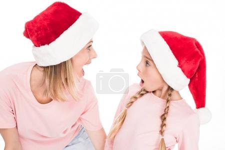 Photo pour Surpris de mère et petite fille en chapeaux santa regardant les uns des autres, isolé sur blanc - image libre de droit