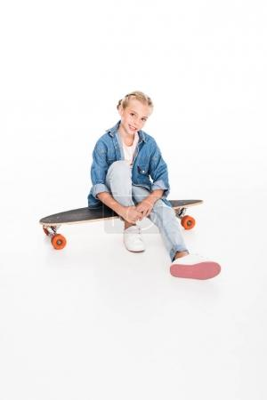 little skateboarder sitting on longboard
