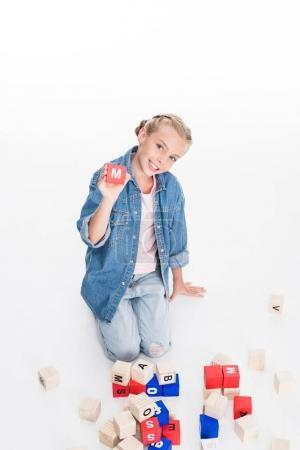 child with aphabet block