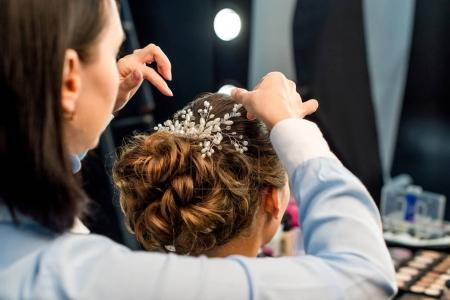 Hairstylist decorating clients hairstyle