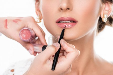 Photo for Close up view of makeup artist applying lipstick using lip brush isolated on white - Royalty Free Image