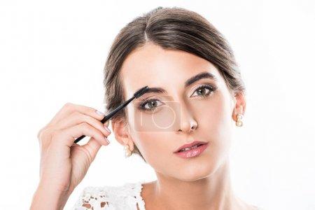 Photo pour Portrait de la belle femme se maquiller avec brosse sourcils isolé sur blanc - image libre de droit