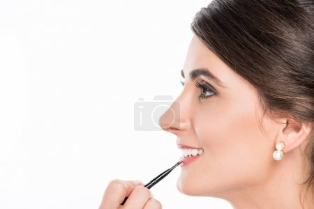 makeup artist applying lipstick on model