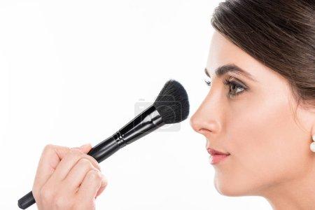 Photo pour Vue partielle du maquilleur, appliquer la poudre sur le visage de modèles à l'aide du pinceau de maquillage isolé sur blanc - image libre de droit