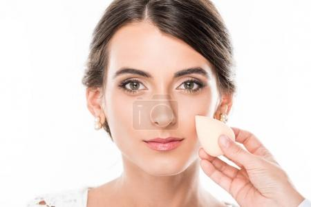 makeup artist applying foundation on face