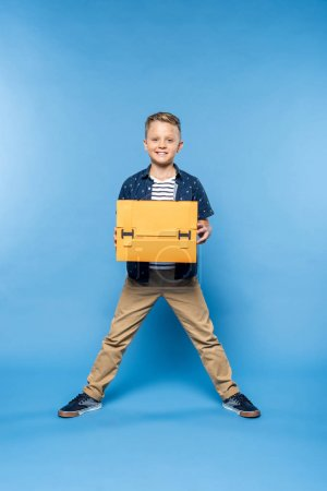 Photo for Happy little boy holding papercraft briefcase and smiling at camera isolated on blue - Royalty Free Image