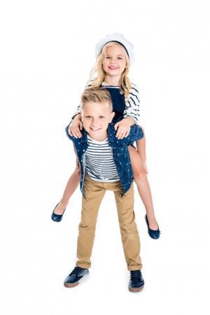 Photo pour Mignon heureux garçon piggybackking adorable petite soeur souriant à caméra isolé sur blanc - image libre de droit