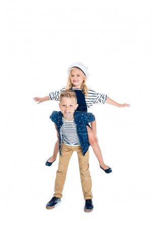 Foto de Muchacho feliz piggybacking adorable hermana pequeña con los brazos abiertos aislados en blanco - Imagen libre de derechos