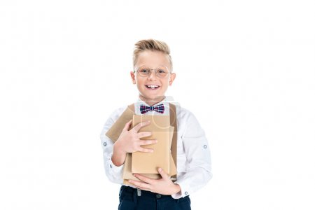 Photo for Cute little boy holding books and smiling at camera isolated on white - Royalty Free Image