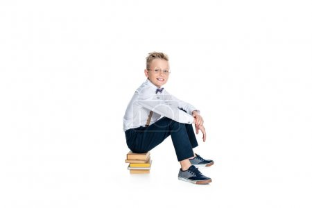 Photo for Happy little boy in eyeglasses sitting on books and smiling at camera isolated on white - Royalty Free Image