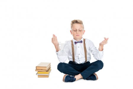 boy meditating with books