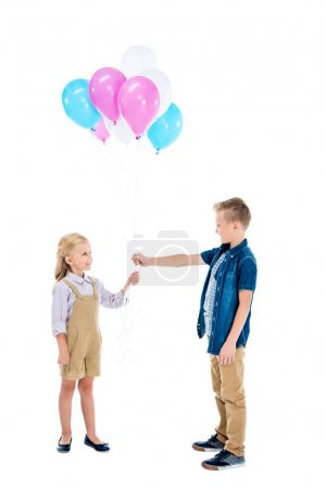 Photo pour Vue latérale de garçon présentant des ballons colorés à mignonne petite fille isolée sur blanc - image libre de droit