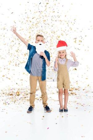 Photo pour Adorables enfants heureux avec chapeau de Père Noël et fausse barbe souriant à la caméra tout en se tenant sous les confettis tombant - image libre de droit
