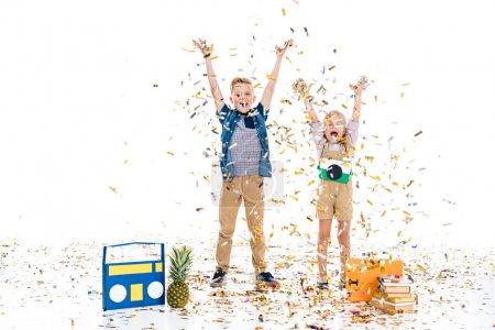 Foto de Niños felices con las manos levantadas de pie entre varios objetos bajo confeti cayendo - Imagen libre de derechos