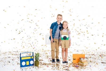 Foto de Niños pequeños felices sonriendo a la cámara mientras están de pie con varios objetos bajo la caída de confeti - Imagen libre de derechos