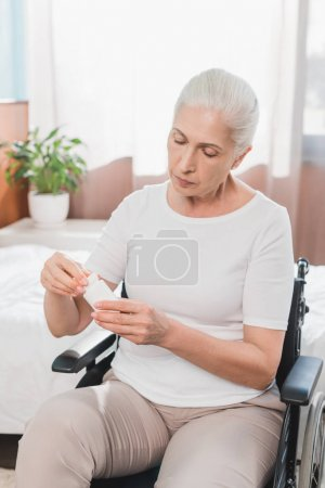 woman in wheelchair taking medicine