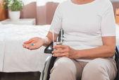 Woman in wheelchair taking medicine