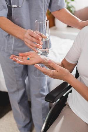 Photo pour Recadrée tir d'infirmière donnant le verre d'eau à haut patient tenant pilule et assis en fauteuil roulant - image libre de droit
