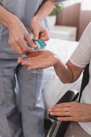 Photo pour Plan recadré de l'infirmière donnant des pilules au patient âgé en fauteuil roulant - image libre de droit