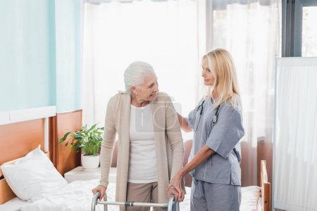 Photo pour Infirmière et femme âgée avec marcheur souriant dans la chambre d'hôpital - image libre de droit