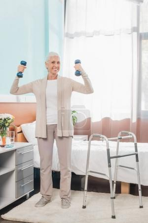 senior woman with dumbbells in