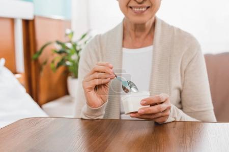 Photo for Cropped shot of smiling senior woman eating yogurt in hospital - Royalty Free Image