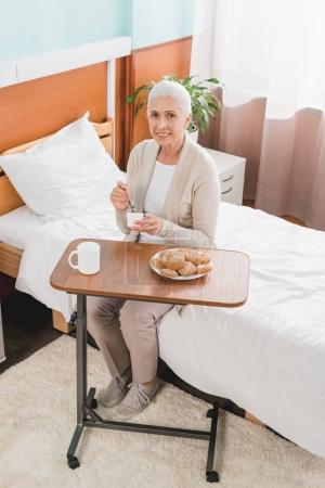 Senior woman eating in hospital