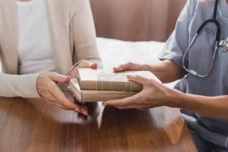 Photo pour Recadrée tir d'infirmière donnant livres hauts patient à la maison de soins infirmiers - image libre de droit