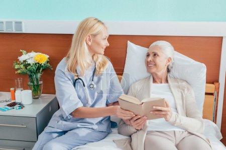 Krankenschwester und Seniorin mit Buch