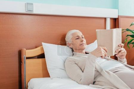 Senior woman with book in hospital
