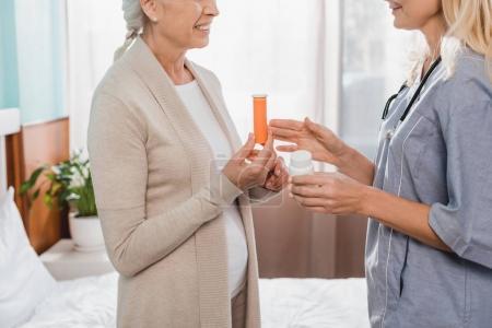 nurse giving medicine to senior patient