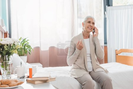 senior woman with smartphone in hospital