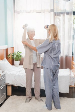 Nurse and senior woman with dumbbells