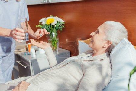 Photo pour Recadrée tir d'infirmière donnant le médicament à souriant patient senior - image libre de droit